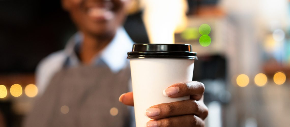 A smiling barista holding out a takeaway coffee towards the camera. Selective focus, with focus on the disposable cup.